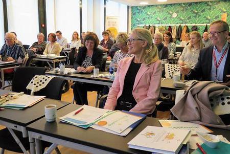 konferansesal med smilende mennesker